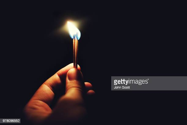 human hand holding lit matches - match lighting equipment stock photos and pictures