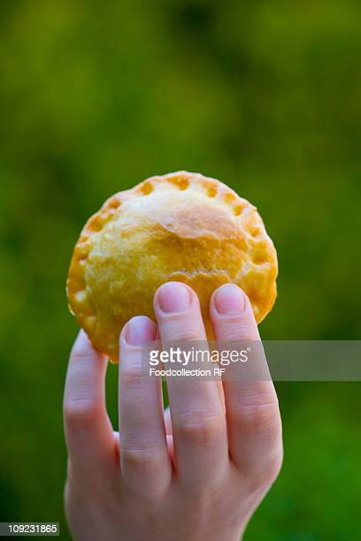 human hand holding meat pie, close-up - cornish pasty stock pictures, royalty-free photos & images
