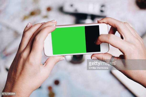 Human hand holding mobile phone with green screen