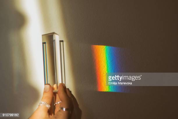 Human hand holding optical prism while making rainbow reflection