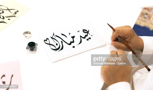 human hand holding pen by paper on table - calligraphy stock photos and pictures