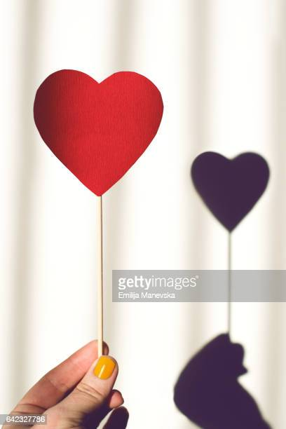 Human hand holding red paper heart