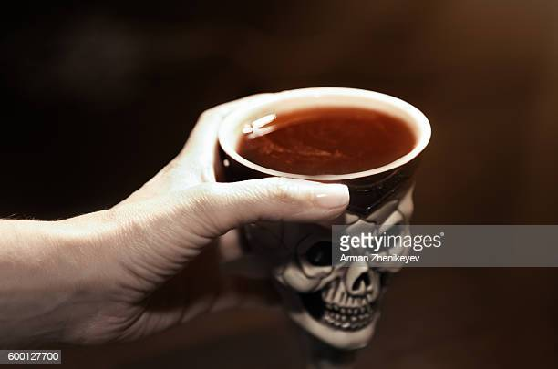 human hand holding skull bowl with poison - ugly witches stock photos and pictures