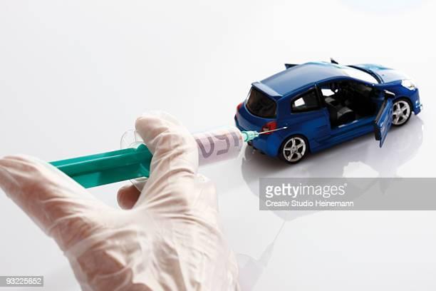Human hand holding syringe injecting on toy car, close-up