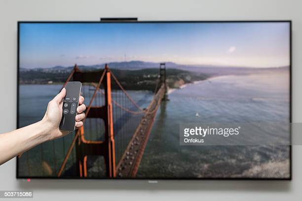 human hand holding the new apple tv siri remote - screen saver stock photos and pictures