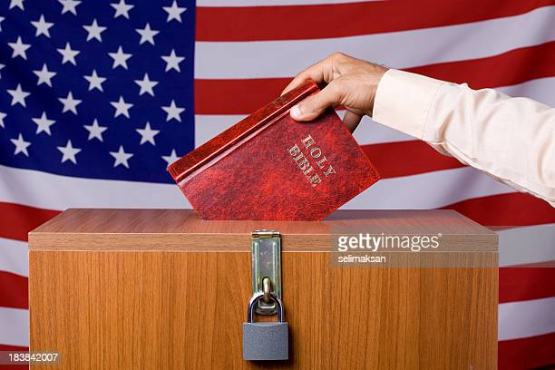 human hand inserting bible to ballot box before american flag - christianity stock pictures, royalty-free photos & images