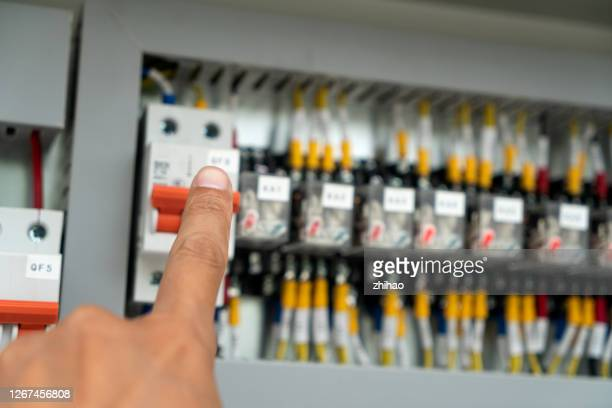 human hand is flipping the power switch in the electrical control cabinet - electrical panel box stock pictures, royalty-free photos & images