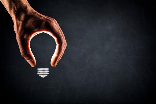 Human Hand Light Bulb on Blackboard - New Idea Glowing 666301072