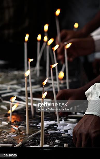 Human hand lighting candles