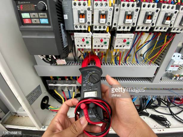 human hand measuring ampere with meter - electrical panel box stock pictures, royalty-free photos & images