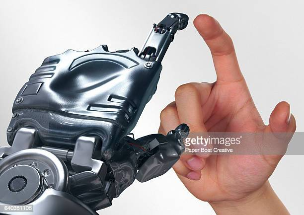 Human hand mirroring the gesture of a robot