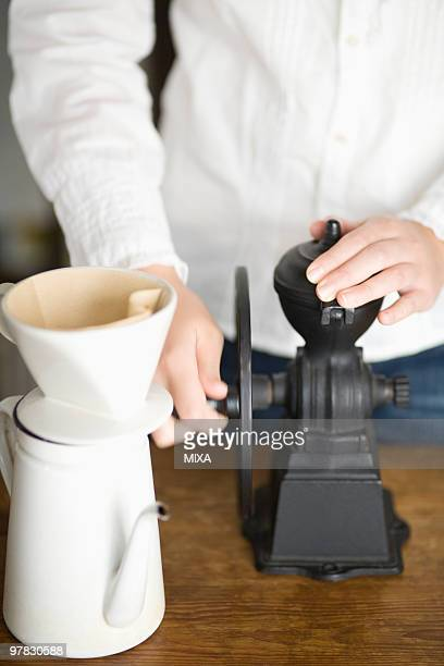 Human hand of young woman grinding coffee mill