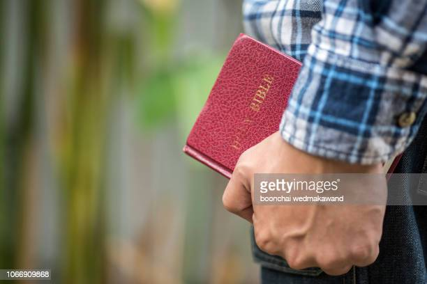 human hand placed on the bible, pray to god. - easter cross stock pictures, royalty-free photos & images