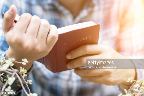human hand placed on the bible, pray to god. - the god father stock photos and pictures