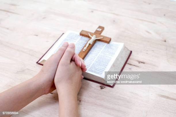 human hand placed on the bible, pray to god. - catholicism stock pictures, royalty-free photos & images