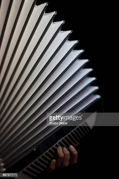 A human hand playing an accordion