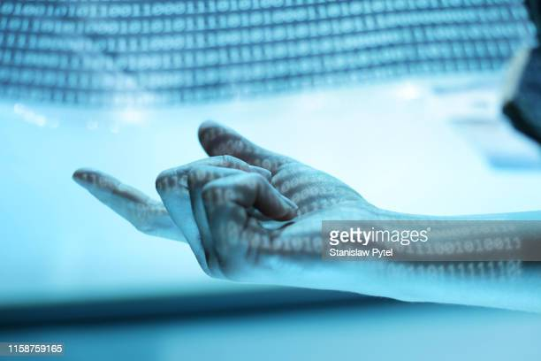 human hand pointing, lit by blue binary code against light background - hand sign stock pictures, royalty-free photos & images