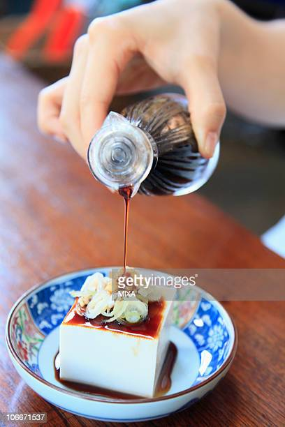 human hand pouring soy sauce on tofu - 醤油 ストックフォトと画像