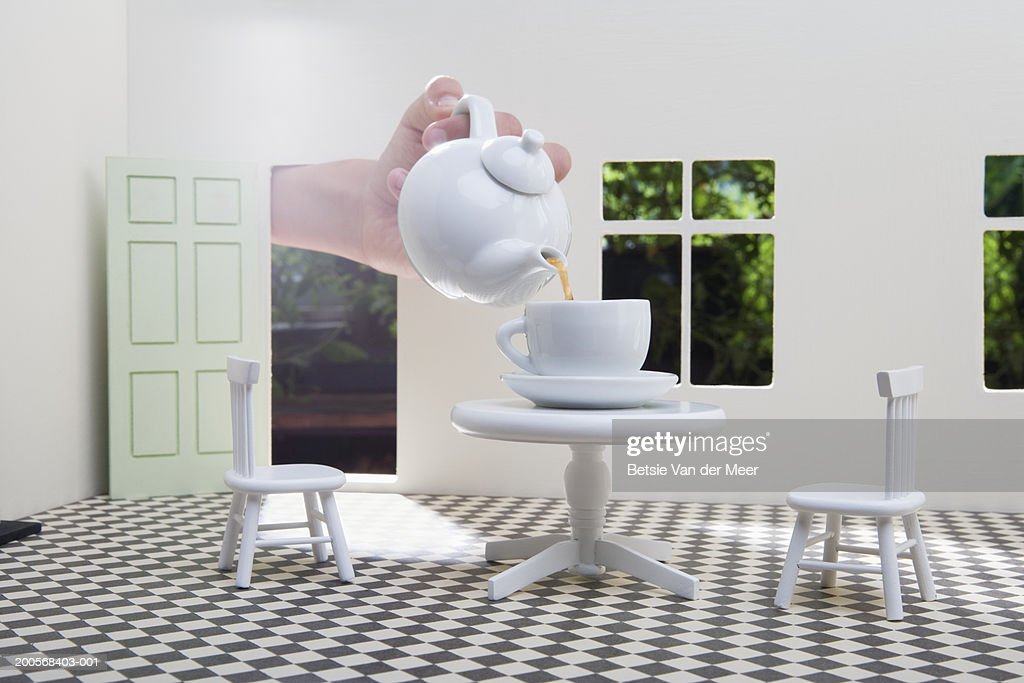 Human hand pouring tea in teacup on table in dolls house, close-up : Bildbanksbilder