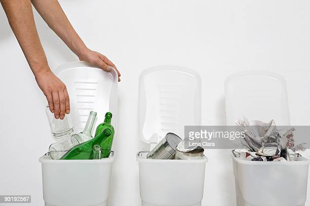 A human hand putting a glass jar in a recycling bin