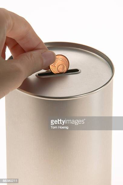 Human hand putting coin in donation tin, close-up