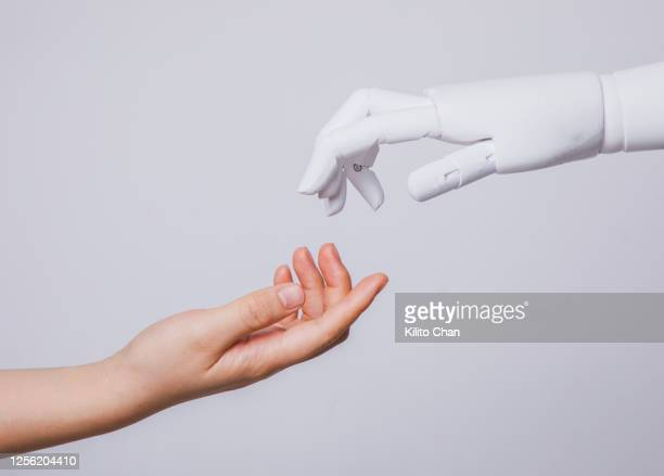 human hand reaching for robotic hand - deep learning stock pictures, royalty-free photos & images