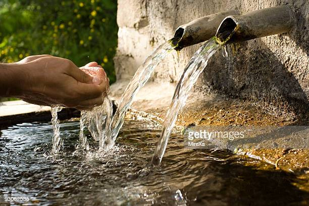 Human hand reaching for water spilling out of stone fountain