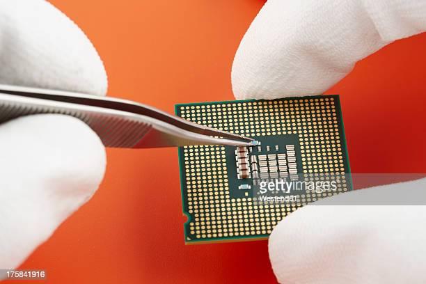 Human hand repairing integrated circuit, close up