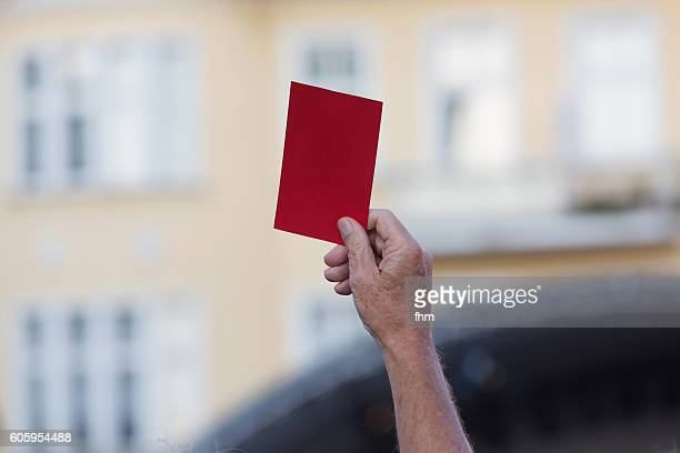 Human Hand showing red card during a demonstration with unsharp facade in the background