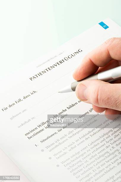 Human hand signing advance directive document, close up