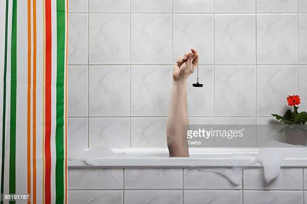 A human hand sticking out of a bathtub holding a bath plug