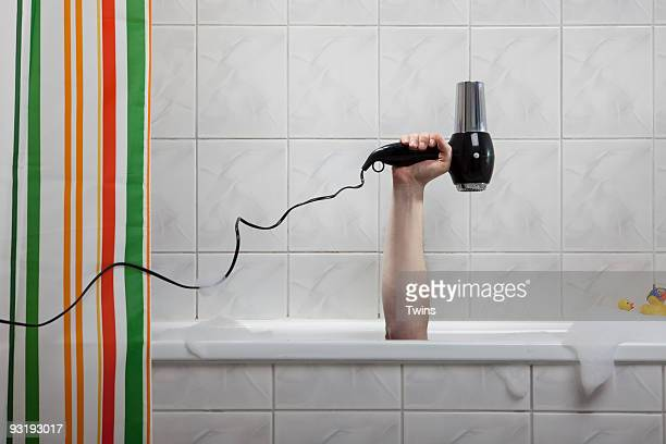 A human hand sticking out of a bathtub holding a hairdryer