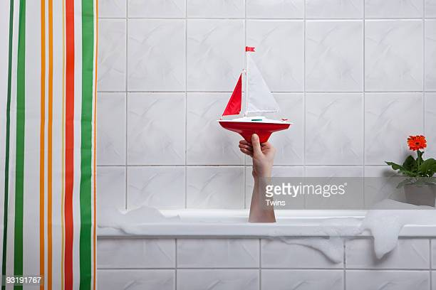 A human hand sticking out of a bathtub holding a toy boat