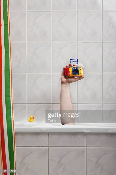 A human hand sticking out of a bathtub holding an underwater camera