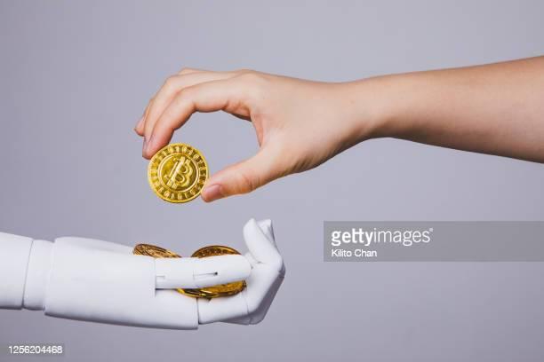 human hand taking bitcoin from robotic hand - 仮想通貨 ストックフォトと画像