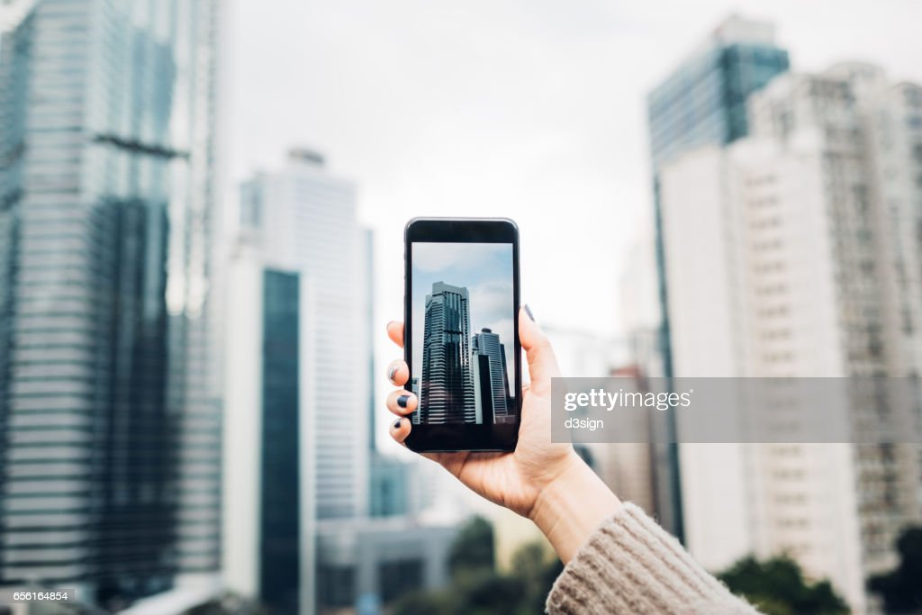 Human hand taking picture with cell phone of downtown modern skyscrapers : Stock Photo