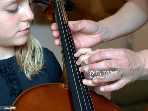 Human hand teaching small child to play cello