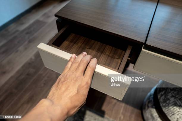 human hand touches desk drawer - drawer stock pictures, royalty-free photos & images
