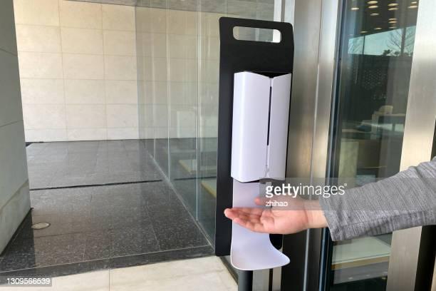 human hand using automatic hand sanitizer dispenser - 消毒薬 ストックフォトと画像