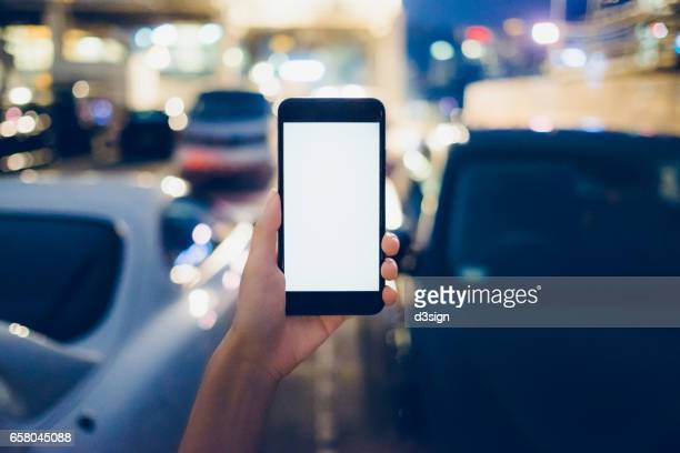 Human hand using cell phone in outdoor car park at night