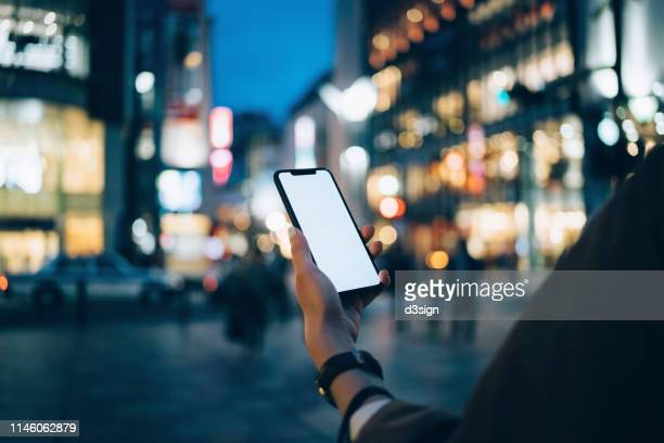 human hand using mobile phone against illuminated neon commercial sign and city street in downtown district at night - スマートフォン ストックフォトと画像