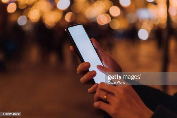 human hand using mobile phone on city street at night - urban road stock pictures, royalty-free photos & images