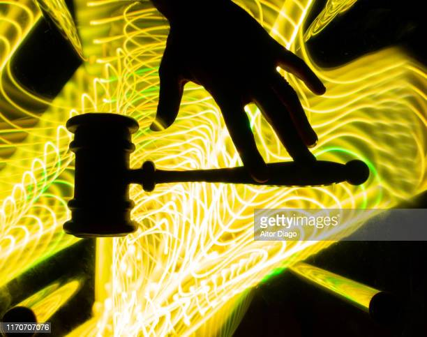 human hand with a judge's hammer  in a futuristic yellow environment.  trial for computer crime - 刑事司法 ストックフォトと画像