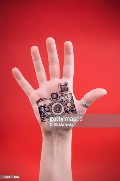 Human hand with drawn vintage camera