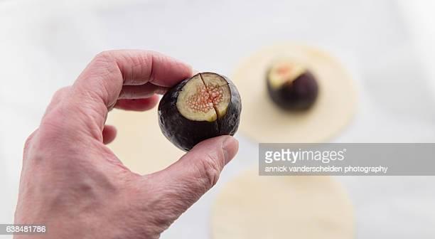 Human hand with fig. Tarte tatin preparation.