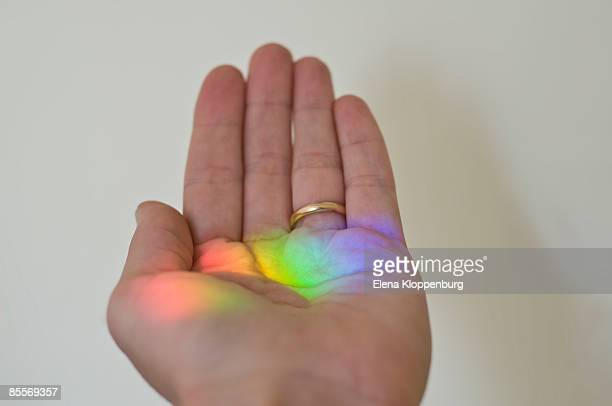 Human hand with rainbow colour prism, close-up