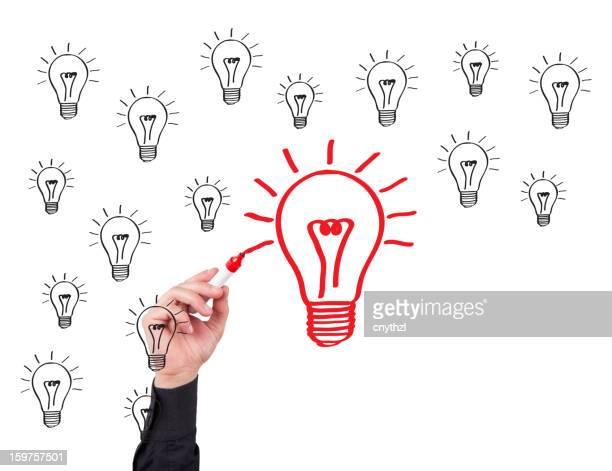 Main de l'homme d'écriture sur tableau blanc et ampoule Concept
