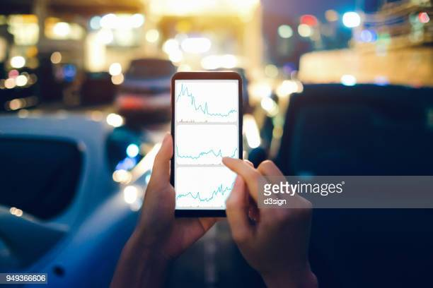 human hands checking financial trading data on mobile phone while walking to car in parking lot - nasdaq stock pictures, royalty-free photos & images