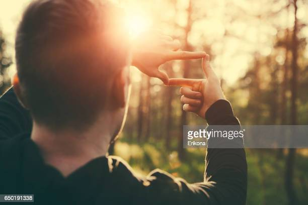 Human hands framing distant sun rays