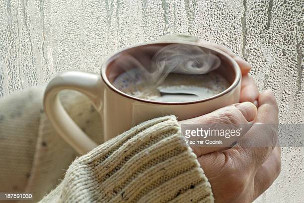 Human hands holding a mug with steam rising up, next to a window with condensation on it